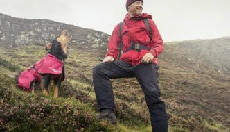 Dog on a mountain wearing a Hurtta Torrent Rain Coat