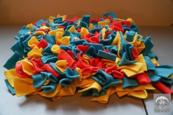 A snuffle mat made of strips of red, yellow, and blue fleece tied together sits on a counter with dog kibble scattered on it.