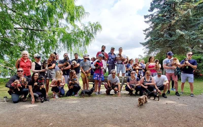 Group photo of the Adventurewiener Club of Seattle members holding their Dachshunds