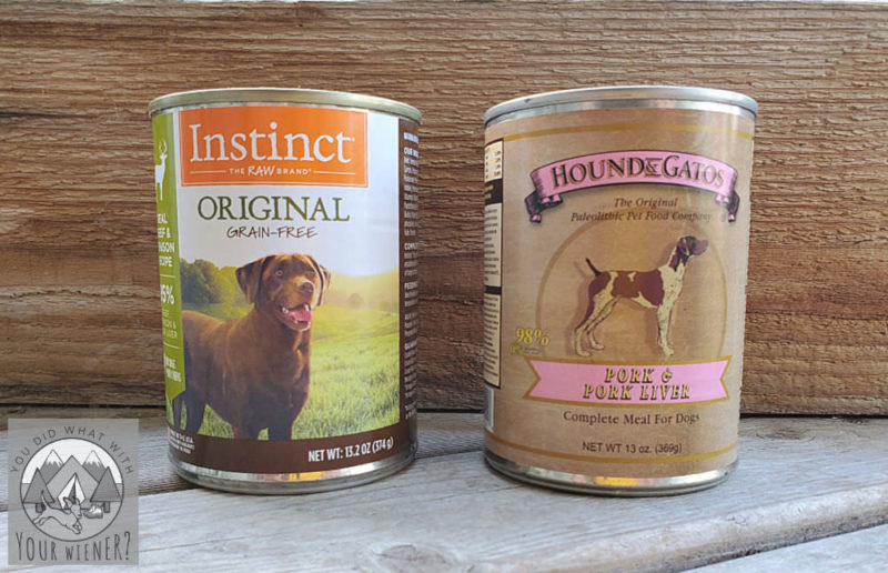 Two cans of Instinct and Hound & Gatos wet dog food