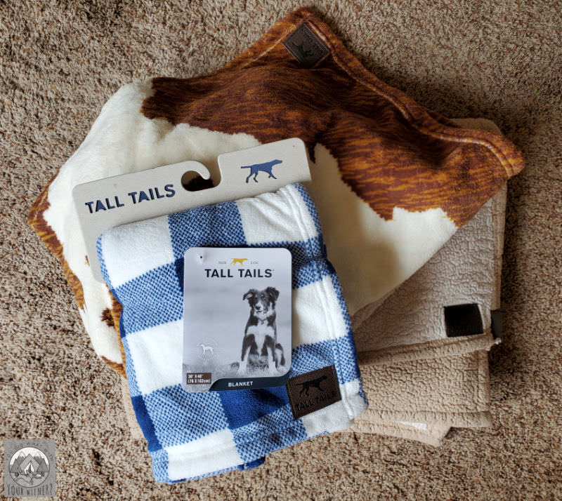 Pile of various dog fleece blankets by Tall Tails